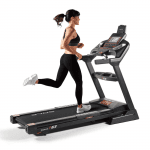 A woman in athletic attire running on the F63 treadmill