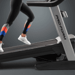 A woman in athletic attire running on the treadmill in an upward angle