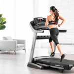 A fit woman in athletic wear running on the Nordictrack 1750 treadmill in a room with a couch and a plant in the background.