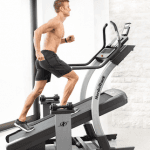 A man in athletic attire running on the Nordictrack x11i incline trainer with 1 weight resting on each side in a bright room with a big window