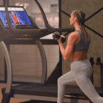 A woman in athletic attire lunging on the Nordictrack x32i incline trainer with a weight in each hand watching a woman fitness instructor on the console. This is taking place in a loft style living space