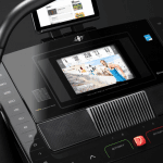 Console screen of the Nordictrack x11i incline trainer with an image of a man running up a road. The incline trainer features a fan, several buttons, 2 cup holders, a speaker and a tablet holder