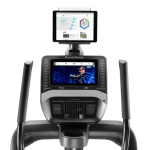 Console of the Nordictrack FS9i trainer with an image of a woman conducting a workout. The treadmill includes a cup holder, a tablet holder, a fan, a speaker and several buttons
