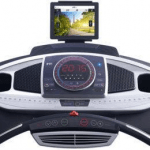 Console of the ProForm Power 995i. This features a digital screen, 2 speakers, 2 cup holders, a fan, a tablet holder and several buttons