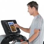 A fit man in athletic attire walking on the Landice L8 LTD Treadmill setting up his workout on the screen with a best Buy Badge