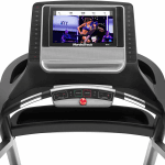 Console screen of the Nordictrack T 9.5 S treadmill with an image of a woman leading a workout. The treadmill features 2 cup holders, several buttons and a speaker