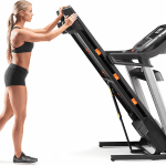 A woman in athletic attire folding the C 990treadmill