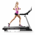 A fit woman in athletic attire running on the ProForm 705 CST Treadmill