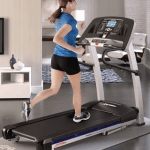 A fit woman in athletic attire running on the Life Fitness F1 Smart Treadmill in a living room setting with a television, 3 bright windows and a chair