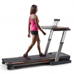 A fit woman in athletic attire walking on the NordicTrack Treadmill Desk Platinum Treadmill watching something on her laptop