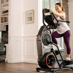 A woman in athletic attire working out on the Bowflex Max Trainer M8 in a living room setting