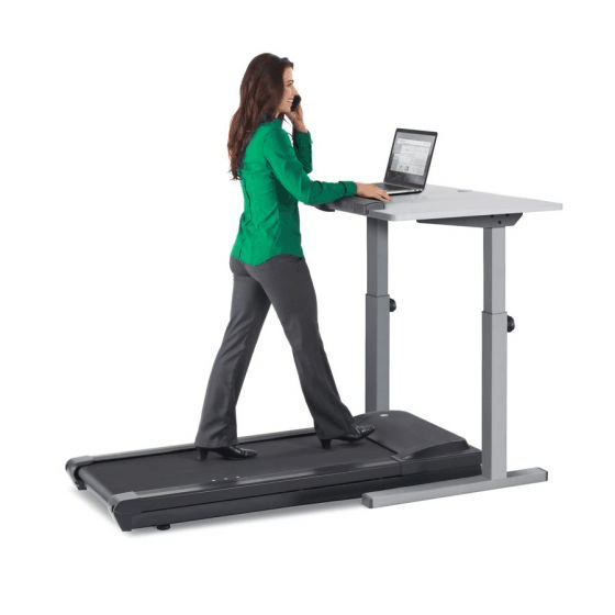 A lady in business casual attire walking on the TR1200 treadmill desk while being on the phone and working on a laptop.