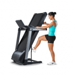 A woman in athletic attire folding the TR3000i treadmill upwards